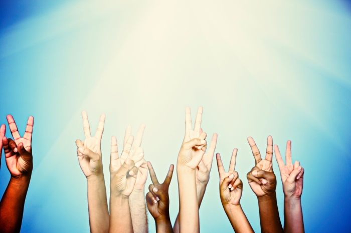 "Many mixed hands all give the ""V"" hand signal indicating Peace or Victory, as they reach up into a heavenly blue background, lit from above and glowing, with plenty of copy space.."